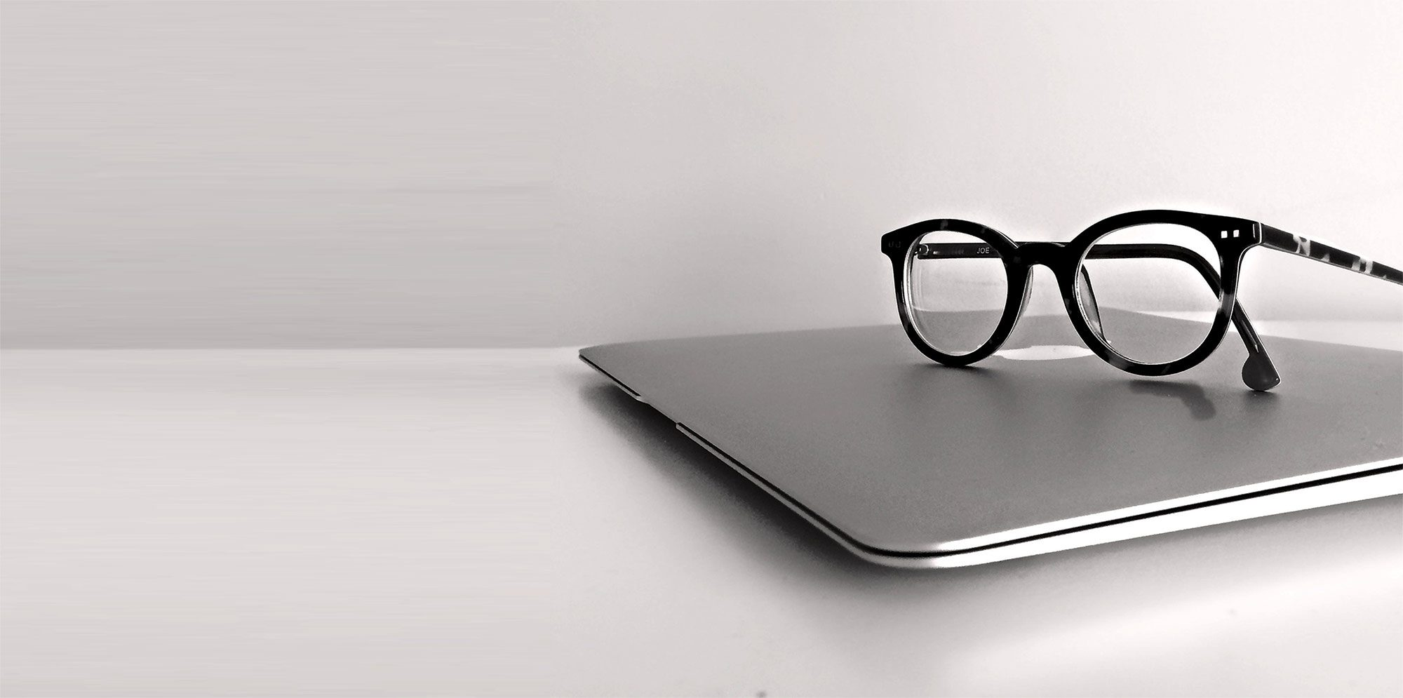 Laptop with reading glasses on top